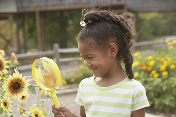 African girl looking at flower through magnifying glass
