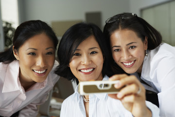 Asian businesswomen taking own photograph