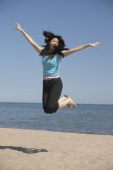 Asian woman jumping in air at beach