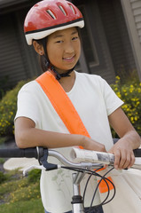 Asian girl on bicycle holding newspaper