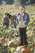 Girl standing on pumpkin in pumpkin patch