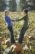 Two girls standing on pumpkin in pumpkin patch