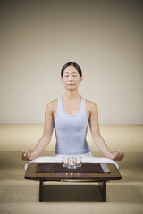 Asian woman meditating with candles
