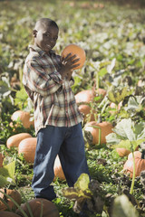 African boy holding pumpkin in pumpkin patch