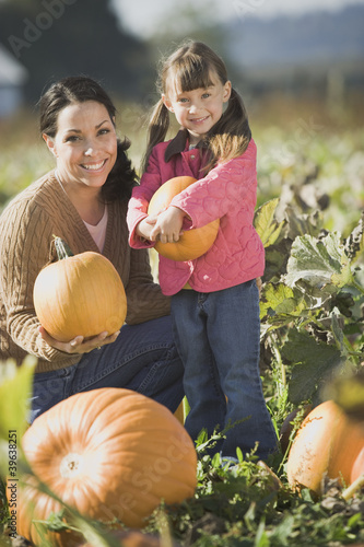 Hispanic mother and daughter in pumpkin patch