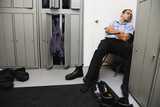 Hispanic male mechanic sleeping in locker room