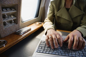 Close up of businesswoman using laptop on private airplane