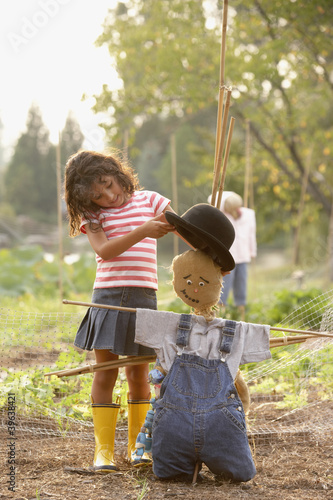 Young Hispanic girl putting hat on scarecrow