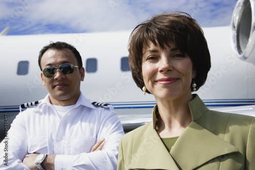 Businesswoman and male pilot standing in front of private airplane