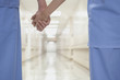 Close up of doctors holding hands in corridor