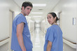 Rear view of male and Hispanic female doctors looking over shoulder in corridor