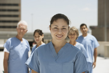Hispanic female doctor smiling with co-workers in background