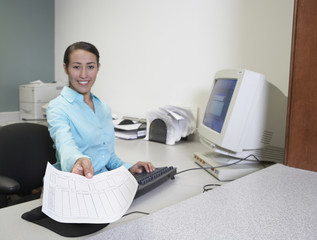 Hispanic businesswoman holding paperwork at desk