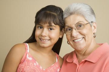 Studio shot of Hispanic grandmother and granddaughter smiling