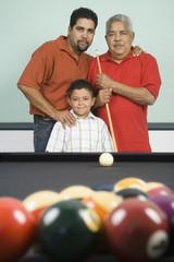 """Hispanic grandfather, father and son playing pool"""