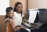 African mother helping daughter with piano lessons