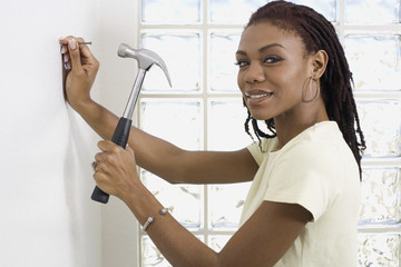 African woman hammering nail into wall
