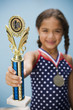 Hispanic girl holding medal and trophy