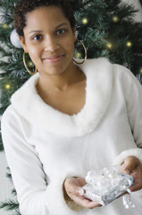 African woman holding gift in front of Christmas tree