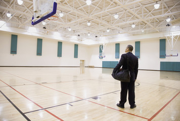 Asian businessman on empty basketball court