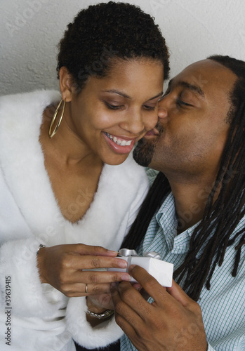 African couple exchanging gift and kissing