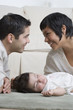 Hispanic parents smiling over sleeping baby