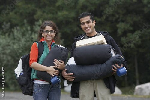 Indian couple carrying camping supplies