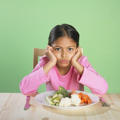 Hispanic girl frowning over plate of vegetables