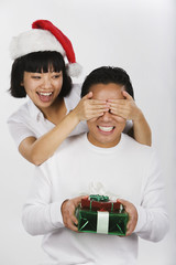Asian woman surprising boyfriend with gift