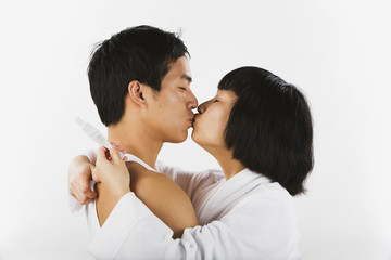 Asian couple kissing and holding pregnancy test