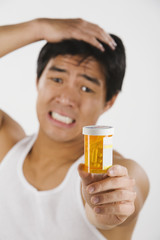 Frustrated Asian man holding medication bottle