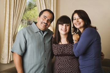 Portrait of Hispanic family hugging