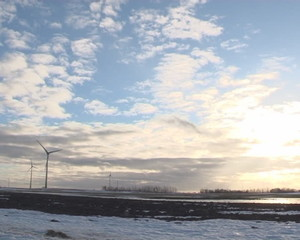 Windmills sky nicely illuminated sun. Melting snow in spring