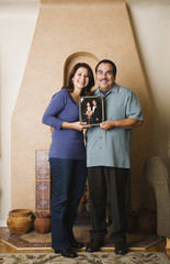 Hispanic couple holding wedding photograph