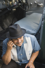 Middle-aged Hispanic man talking on cell phone in classic car