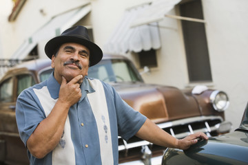 Middle-aged Hispanic man in front of classic car