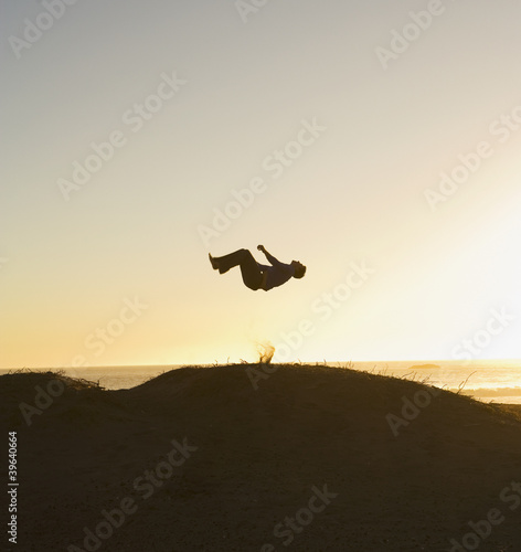 Silhouette of person doing flip on hill