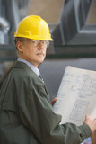 Businessman in hard hat holding blueprints