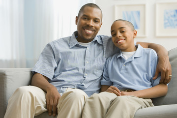 Portrait of African father and son on sofa