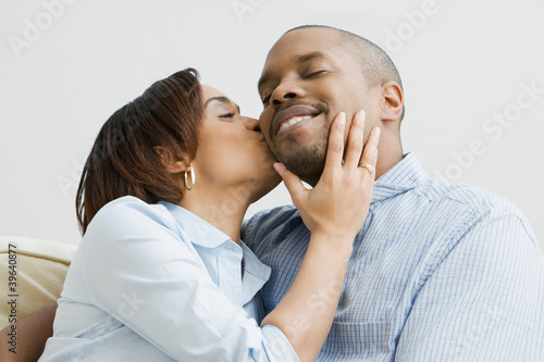 African woman kissing husband on cheek