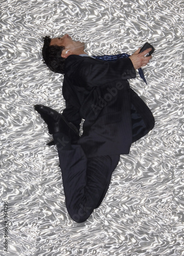 Hispanic businessman jumping and listening to music