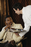 Waiter bringing African man a drink