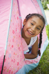 Portrait of African girl leaning out of tent