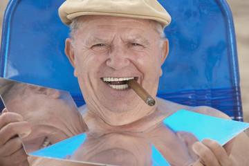 Senior man smoking cigar and sunbathing