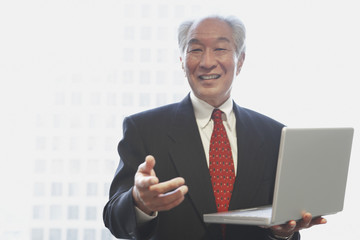 Senior Asian businessman holding laptop
