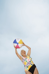 Senior woman holding beach ball