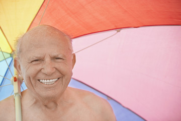 Senior man holding beach umbrella