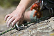 Hand of climbing man with carbine and rope