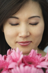 Asian woman smelling flowers