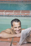 Hispanic man reading newspaper in swimming pool
